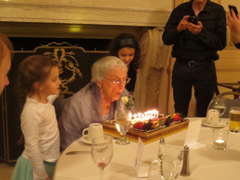 Two granddaughters watch Janet with her cake